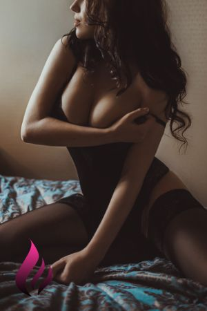 Passion kneels on the bed in black lingerie covering her breasts