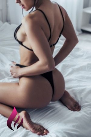 Bella kneels on the bed barefoot and showing sideboob wearing black lingerie including a black thong