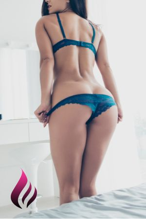 Julia wearing blue lingerie standing next to the bed pulling down her panties