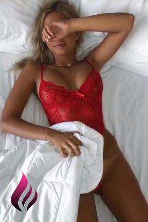 Birmingham escort Lucy lies on her back on the bed covering her eyes wearing a red dress